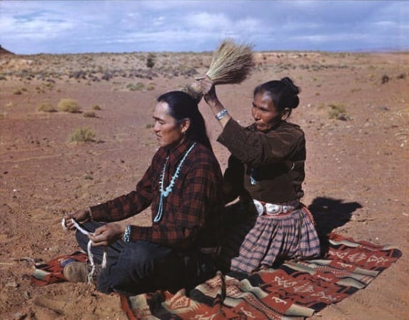 Navajo Barber Shop. An Indian women dresses her husband's hair as they sit on the desert floor in the open-air-living room. The man holds the string with which the women will bind his locks. Doing each others hair is a sign of affection for each other. Photo and Caption by Josef Muench